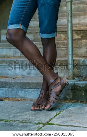 Close up of african black african american man legs, while wearing blue jean shorts and brown sandals - stock photo