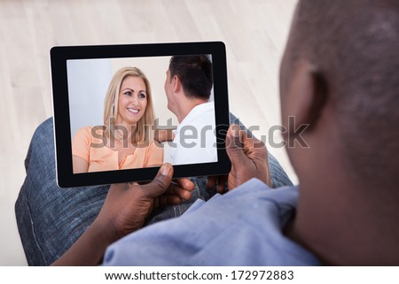 Close-up Of African Man Watching Video On Digital Tablet - stock photo