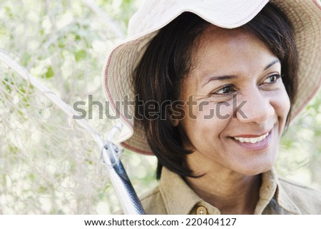 Close up of African woman smiling and holding net - stock photo