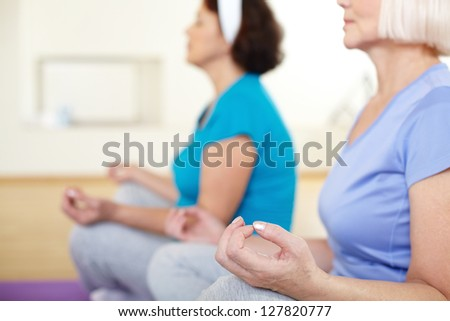 Close-up of aged female doing yoga exercise in sport gym - stock photo