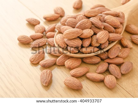 close up of almonds pile in a wood spoon on wood background - stock photo