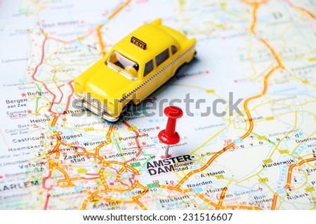 Close up of  Amsterdam , Netherlands  map with red pin and a taxi  - Travel concept - stock photo