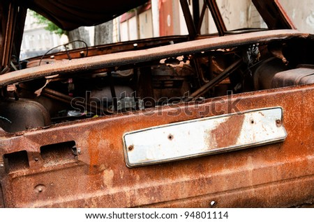 close up of an abandoned rusty car with a empty license plate after a fire - stock photo