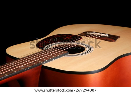 Close up of an acoustic guitar set against a black background   - stock photo