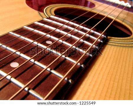 Close up of an acoustic guitar. Strings frets and sound hole. - stock photo
