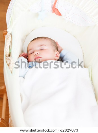 Close-up of an adorable baby sleeping in his cradle at home - stock photo