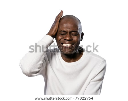 Close-up of an afro American man with a severe headache in studio on white isolated background - stock photo