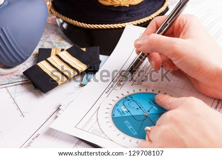 Close up of an airplane pilot hand filling in an flight plan with equipment including hat, epaulettes and other documents in background - stock photo