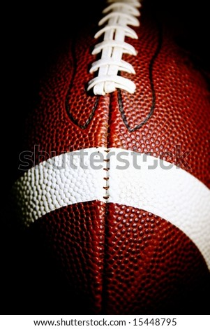 close up of an american football against a black background vertical - stock photo