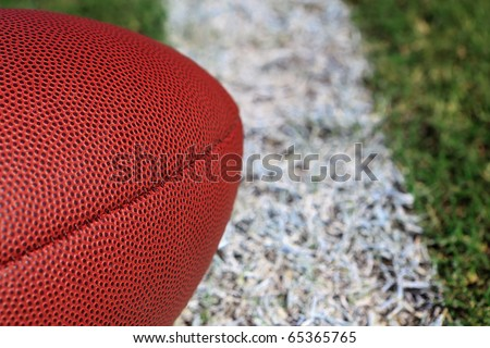 Close-up of an american football on a grass field. - stock photo