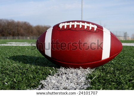 Close up of an american football on the field - stock photo