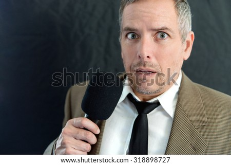 Close-up of an anxious man speaking into microphone. - stock photo