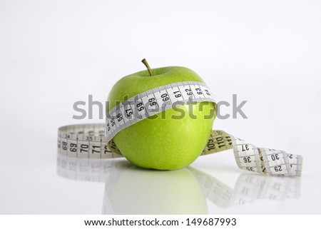 Close-up of an apple with a measuring tape around it at the background. - stock photo