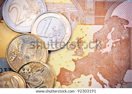 Close-up of an assortment of Euro coins on a Euro bill background with a map of Europe. - stock photo