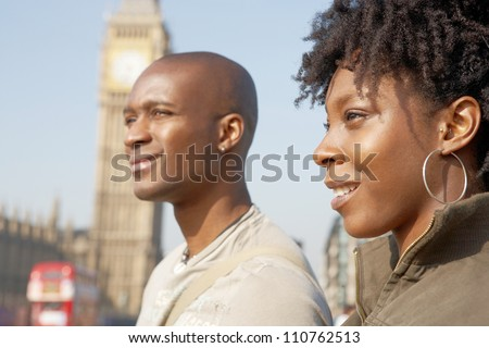 Close up of an attractive black tourist couple walking past Big Ben while visiting London city on vacation, smiling. - stock photo