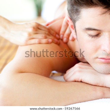 Close-up of an attractive man having a back massage in a spa center - stock photo