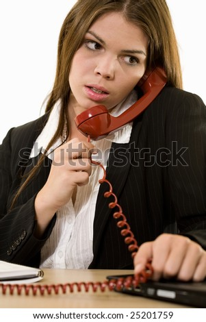 Close up of an attractive young brunette woman in business suit talking on an old style red phone while sitting at a desk - stock photo