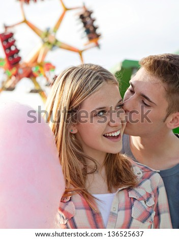 Close up of an attractive young couple kissing while visiting a funfair amusement park arcade with rides and holding a pink cotton candy floss sweet. - stock photo