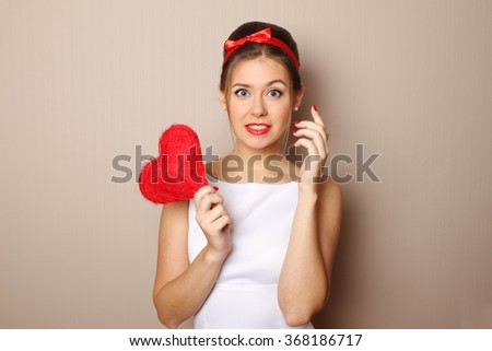 Close up of an attractive young woman holding a red heart. - stock photo