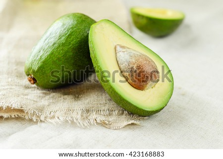 Close-up of an avocado on wooden table. Healthy food concept. - stock photo