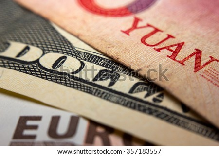 Close-up of an Chinese yuan, an American dollar and a Euro banknote - stock photo