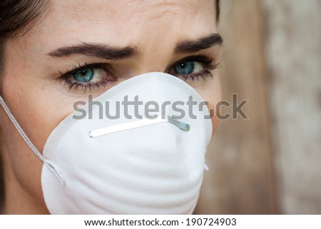 Close-up of an concerned woman wearing a face mask to protect herself from infection or air pollution. - stock photo