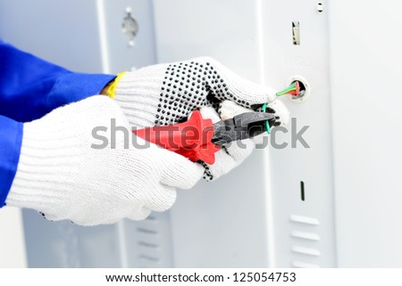 Close-up of an electrician using nippers to cut wires - stock photo
