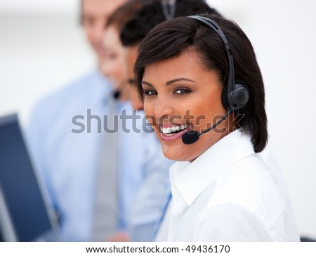 Close-up of an ethnic customer service agent and her team against a white background - stock photo