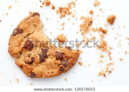 Close up of an half eaten cookie with crumb against a white background - stock photo