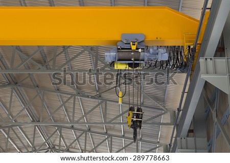 Close up of an indoor factory overhead crane on a yellow beam - stock photo