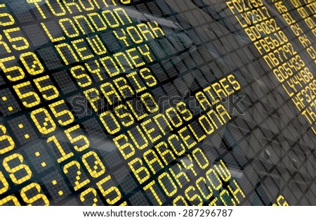 Close-up of an international airport departure board with environment reflection.Part of a series. - stock photo