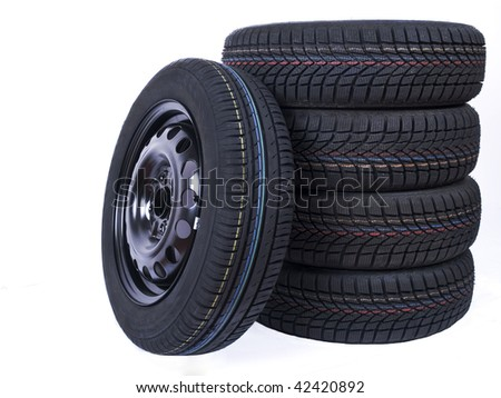 Close up of an isolated wheel and stacked tyres - stock photo