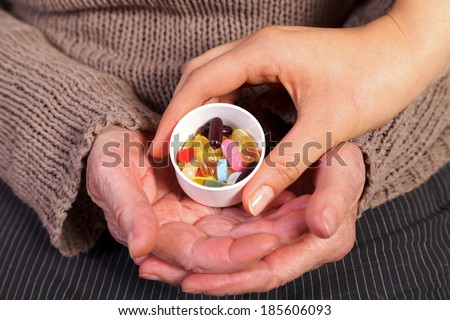 Close up of an nurse's hand giving pills to an elderly woman. - stock photo