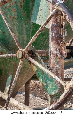 Close-up of an old, dirty, rusty, green concrete bucket with hand wheel and sagging suspension, taken at a construction site in Germany.  - stock photo
