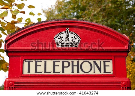Close up of an old English red telephone box during autumn - stock photo