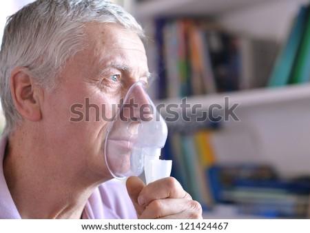close-up of an old man doing inhalation - stock photo