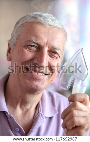 close-up of an old man with an inhaler in hand - stock photo