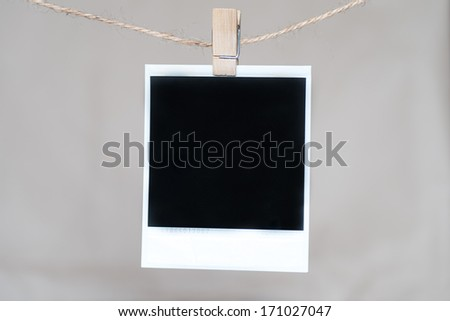 Close up of an old photo and clothes peg on a wall background - stock photo