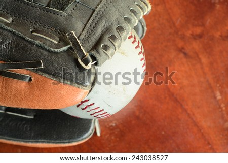 Close up of an old softball in a glove on a wooden surface - stock photo