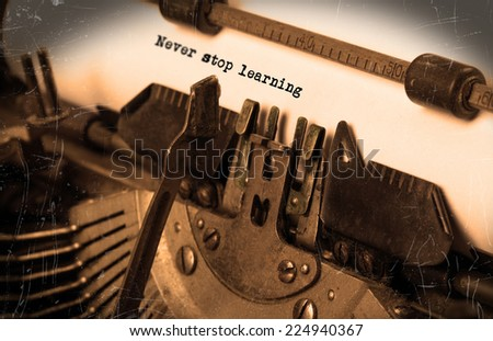 Close-up of an old typewriter with paper, selective focus, Never stop learning - stock photo