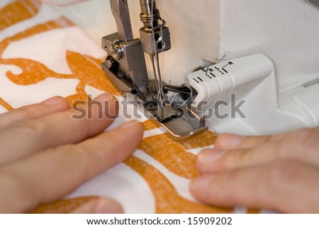 Close up of an overlock sewing machine in use - stock photo