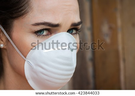 Close-up of an unhappy woman wearing a face mask to deal with virus or pollution. - stock photo