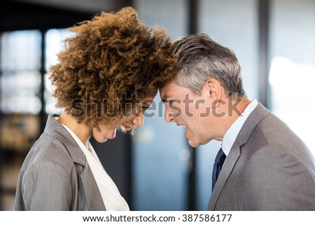 Close-up of angry businessman and businesswoman standing head to head - stock photo