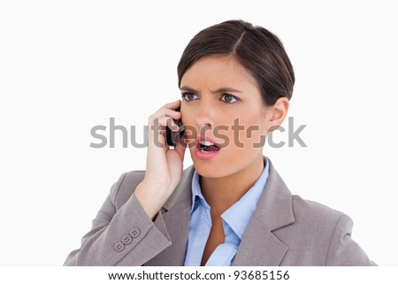 Close up of angry entrepreneur on her cellphone against a white background - stock photo
