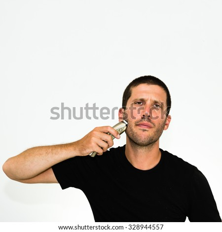 Close-up of annoyed young man shaving with electric razor wearing black tshirt - stock photo