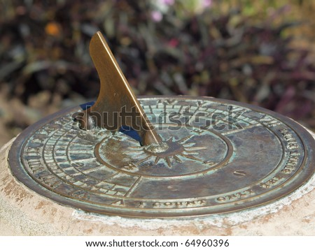 Close-up of antique sundial decorating a garden - stock photo