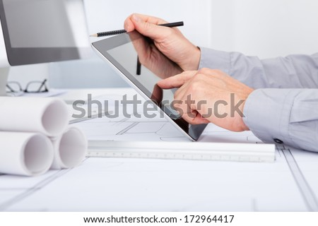 Close-up Of Architect Using Digital Tablet Over Blue Print - stock photo