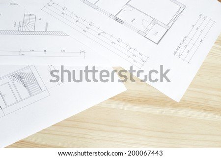 Close-up of architects blueprint over wooden table. - stock photo