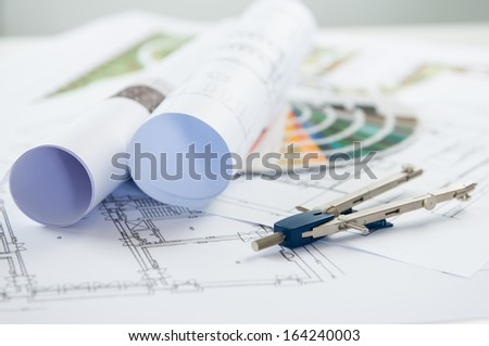 Close Up Of Architectural Blueprints And Compass On Desk - stock photo