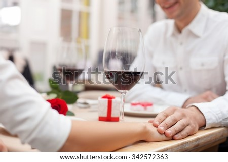 Close up of arms of cheerful loving couple holding hands in cafe. They are drinking wine and sitting at table. The man is smiling - stock photo